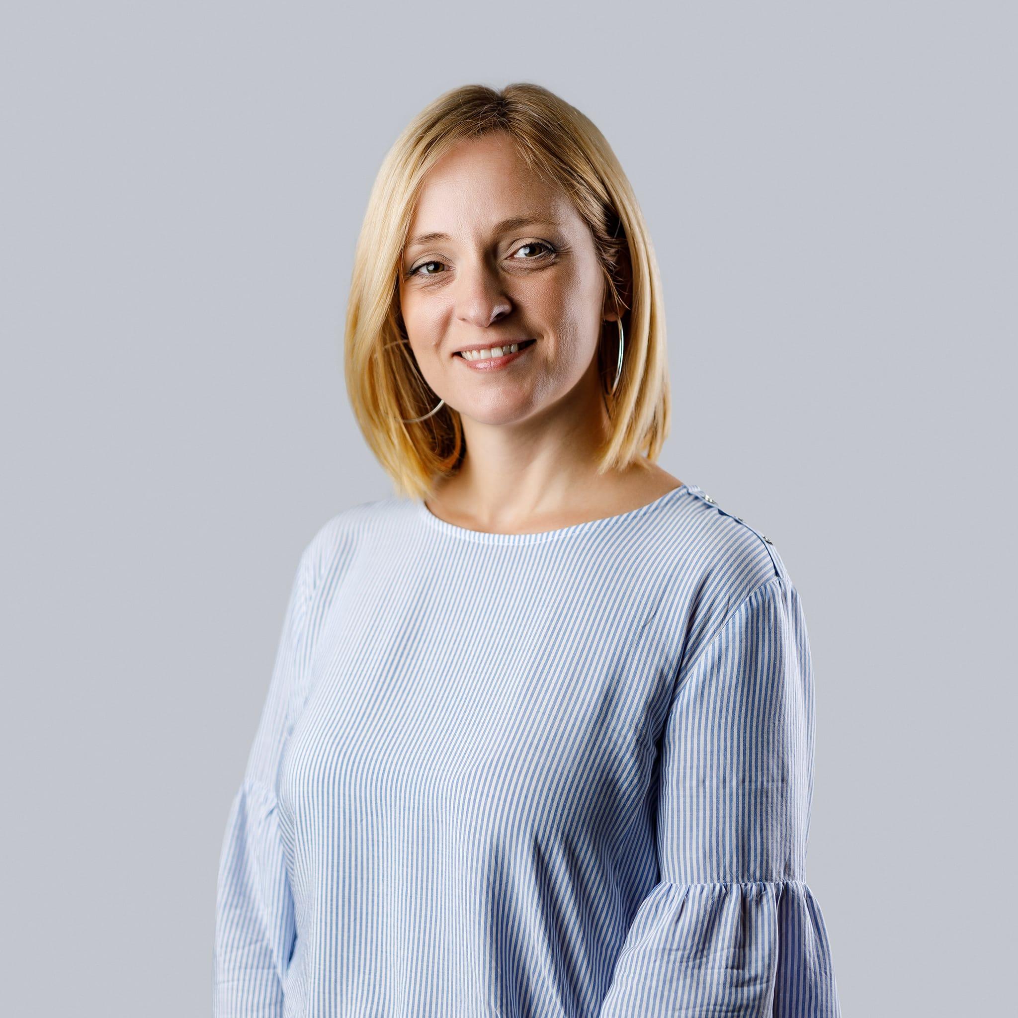 Poslovni portret mlade, plave žene u plavoj košulji.